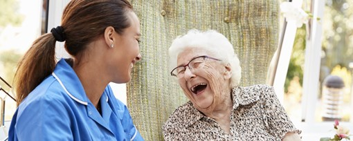 An elderly woman sat in a garden laughing with a care worker.