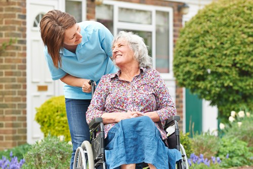 A carer and a woman in a wheelchair in the garden together